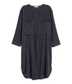 En rak klänning i vävd viskos. Klänningen har rund halsringning med dold knäppning upptill. Bröstfickor och trekvartslång ärm. Slits i sidorna. Ofodrad.