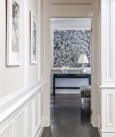 Chic hall boasts a black and white photo gallery over wainscot trim.