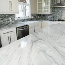 features a soft white background with subtle gray swirls making it a timeless addition to any space. Come and see us where located at 12301 Metro Parkway Fort Myers, FL Granite Kitchen, Kitchen Flooring, Kitchen Countertops, Kitchen And Bath, New Kitchen, Kitchen Reno, Kitchen Ideas, Quartzite Countertops, Kitchen Island With Seating