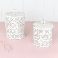 These 2 metal lace storage boxes are crafted from intricately cut metal complete with lid. Finished with a distressed ivory coating revealing the natural brown colouring creating a rustic aged feel to the set, complete with crystal cut acrylic handles. Perfectly sized storage boxes, suitable to store cotton wool or jewellery. Find these at www.dibor.co.uk