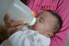 This tiny little one has a bottle while waiting to be examined for cleft surgery in Kaifeng!