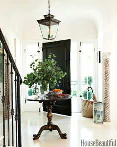 "To create a light, airy feel in the entry of his West Hollywood house, visual merchandiser Mark D. Sikes painted the walls New Linen by Kelly-Moore and whitewashed the floors. For a dramatic ""Dorothy Draper moment,"" he used Benjamin Moore's high-gloss Black on the door."