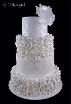 Scrunch/ruffle flowers made from fondant adorn two tiers of this...