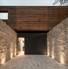 A massive stone wall on the street shields the home's occupant from the public; the front door opens onto the second-floor living area.