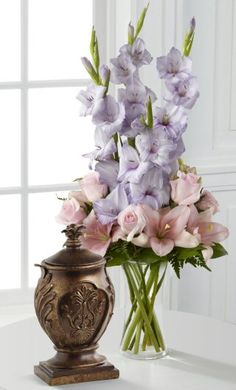 A vase arrangement of gladiola, roses and asiatic lilies.
