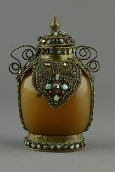 Well hollowed Agate snuff bottle with silver mount, of flattened flask form, the body framed with intricate silver designs inlaid with turquoise, turquoise and coral insets. H: 12 cm, W: 7 cm, 298 grams.