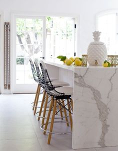 Calacatta Gold marble, waterfall edge, and Hello big pineapple jar! (AlsoI would like to have those stools, please.)