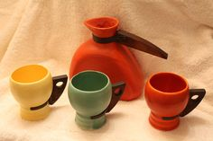 California art deco Tudor potteries carafe with multi colored wood handled mugs from the 1930s.