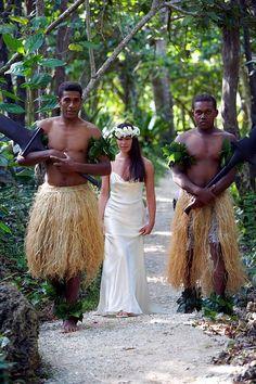Fijian warriors lead a beautiful bride to her future husband
