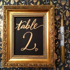 Wedding table number in a gold frame using a gold sharpie on chalkboard paint. A simple, modern calligraphy style has been used. See more at www.facebook.com/emeraldpaperdesign or www.instagram.com/emeraldpaperdesign