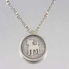 Jack Russell silhouette was hand sawed out using a jewelers saw with a small saw blade, then the circle pendant was formed using raw metal (sterling silver) material. Personal touch includes stamping