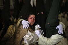 """A crying woman is comforted by fellow penitents inside a church where they took shelter from the rain during the """"Lagrimas y Favores"""" (Tears and Favors) brotherhood Palm Sunday procession in Malaga on March 24, 2013"""