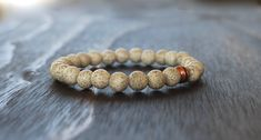 Men's Beaded Lotus Seed Bracelet with Copper Accent  **Like the lotus flower, which grows and blooms in muddy water, the lotus seed symbolizes spiritual growth and the ability to rise above obstacles. It is also said to increase one's devotion, peace of mind, and inner beauty.**  MATERIALS: ~8mm lotus seed beads ~Tierra Cast copper grooved bead  DETAILS:  ~8 inches in length. This is a standard men's size but can be made any size. ~Strung on high quality jewelry cord for a continuous look…