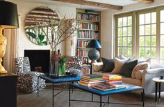 Cozy Corner - Bungalow throw pillows complement a linen-covered sofa. Round Deco mirror is through Privet House. Vintage 1970s black-and-white slipper chairs were found at 1stdibs. Custom tables are topped with Edelman blue croc leather. Bookshelves are custom by SM Carpentry, LLC. Designed by Bruce Beinfield