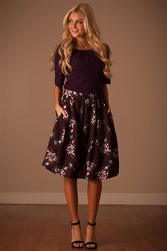 We just love this skirt! Stunning metallic black, full skirt, features a bright and colorful floral print, front pockets, elastic back waist and side zipper closure.