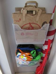 plastic file boxes into wall-mounted bins to store our reusable grocery sacks and paper bags.