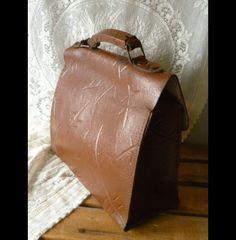Eine alte Aktentasche aus echtem, rotbraunem Leder - vorne mit einem Clipverschluß und zwei niedlichen Drehverschlüssen. Das Leder ist aussen mit einem Muster geprägt.  Kann man auch als Vintage...