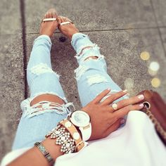 A bit of Bohemia. Ripped light wash skinny jeans with folded ankle, gold strap sandals, tons of gold bracelets and rings, turquoise, watch, all paired with white flowy top and dark brown shoulder bag.