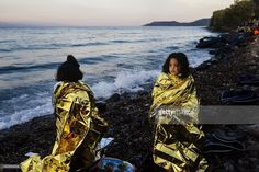 Children stand on a beach wrapped in emergency blankets shortly after arriving…