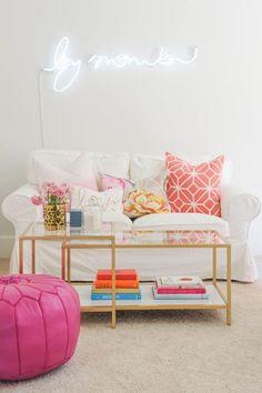 Ambiance girly dans ce salon, le pouf rose apporte du pep au look immaculé du canapé