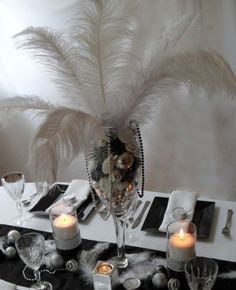Black and silver centrepiece with candles and white feathers