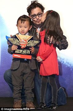 """Johnny Depp greets two children in Beijing, China during a press conference for the movie """"Transcendence"""" on 3/31/14."""