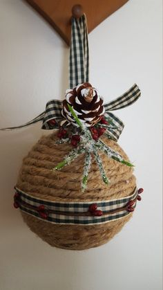 Jute Christmas ball with Pine Cones and Berries: * Styrofoam Ball * Jute rope * Green and Cream plaid ribbon * Pine Cones * Red Berries 7 x 6 x 6