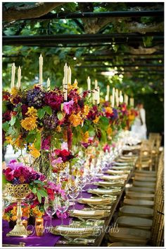 Opulent wedding reception table with tall golden candelabras and vessels with lush hydrangea, peony, dahlia, and orchids. Magenta violet table runner www.cvlinens.com