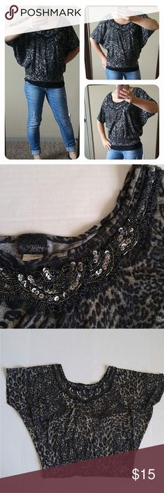 """Daytrip Dolman Batwing Shimmer Metallic Animal Med Cute, fun and sparkly dolman batwing sleeve top from Daytrip! This is a gray and black metallic shimmer fabric with an animal print (leopard, cheetah?). Very pretty beaded neckline. There is a strand of beads missing, that's not even noticeable unless you are looking for the pattern. Banded waistband. Approximately 20"""" Long. 96% Polyester 4% Spandex. Size Medium from Daytrip Daytrip Tops"""