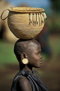 A young Mursi Girl with a beautiful hand made basket on her head. Lower Omo valley Ethiopia