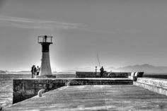 A fisherman makes his morning catch next to a lighthouse Multiple Exposure, Dynamic Range, Hdr, Cn Tower, Lighthouse, Shots, Lighting, World, Building