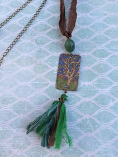Double sided 40x24mm embossed and patinated Vintaj antiqued copper pendant. Side 1 embossed with raised tree and grass of natural copper with background