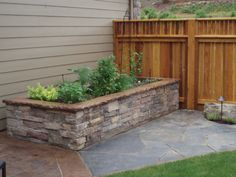 Raise vegetable bed with cultured stone side walls and fitted iron mt stone pathway.