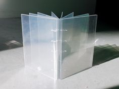 Clear laser-cut acrylic covers and Duralar acetate pages coptic-bound together with clear fishing line
