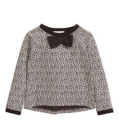 Soft jacquard-knit top with long sleeves, bow appliqué at front, and rounded hem. Slightly longer at back.