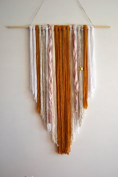 This handmade yarn and wooden dowel tapestry hanging is great for a statement piece or room decor.    Each piece is made by hand so the finished