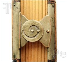 Photo of brass spiral book clasp detail from an antique photography album with gilded pages and leather cover
