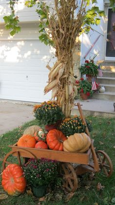 wooden wagon filled with mums & pumpkins; corn stalk wrapped tree