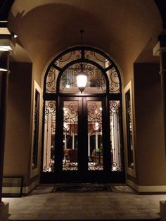 Took some significant man - and machine!- power to install this incredible, custom, wrought iron door.  But the finished product was well worth the effort! Simply stunning. front doors. entry doors. iron doors. wrought iron door. unique door. home remodel. dream home. custom doors.