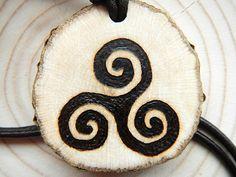 Amulett aus heimischem Astholz aus der Region mit einem durch Brandmalerei verziertem Triskele-Motiv.