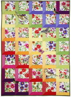 """The butterfly and bird appliques which are added to this attic windows style quilt turns it into a beautiful garden themed quilt. Finished Size: 40"""" x 56""""."""