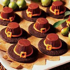 "16 chocolate wafer cookies (such as Nabisco Famous Chocolate Wafers) 1 tube orange frosting with piping tips 16 small peanut butter cups  Place cookies on work surface; squeeze a dime-size dot of frosting in center of each Unwrap and invert peanut butter cups on frosting, pressing down gently Using the round piping tip, pipe a ""hat-band"" with frosting around peanut butter cup and a square ""buckle."" Let frosting set before storing."