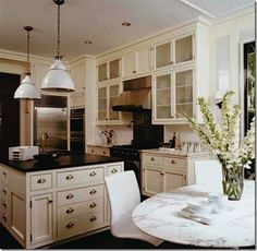creamy white kitchen with dark countertops, pretty glass-front cabinets, awesome pendants, and big square island...and love the #Saarinen tulip table