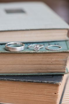 The bride and groom's white gold metal and diamond wedding rings. A detail photo with vintage books my Mikkel Paige Photography.