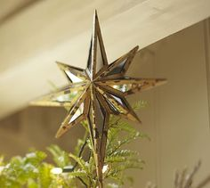 """Mirrored Star Tree Topper #potterybarn Sixteen mirrored glass panes are hand cut and framed with a rustic gilt finish to make our spectacular tree topper, which is designed to resemble the North Star. 13"""" wide x 3"""" deep x 23"""" high Iron metal with a gold finish inset with mirror-glass panes. Cone holder fits securely on top branch of your tree."""