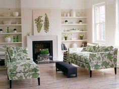 living room design with fireplace, green upholstered furniture and buit in shelves