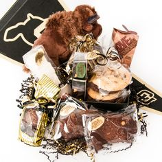 "This CU Buffaloes Gift Basket was designed for chocolate lovers. Beautifully packaged in CU regalia, this basket includes:  6 PL&C Signature Cookies  2 Peanut Butter Buffanutters 3 PL&C Sweet & Salty Brownies 1 12 piece box of our Signature Salted Liquid Caramels 1 package of PL&C Salted Caramel Marshmallows 1 PL&C Hot Chocolate Mug 1 box of PL&C Signature Sipping Chocolate 3 – piece box of PL&C ""Truffaloes"" 3 PL&C Chocolate Butter Buffalo Cookies"