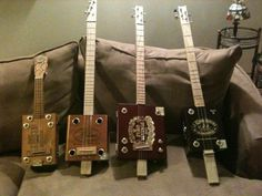 A ukulele, a 3 string slide guitar, a 4 string tenor guitar, and a 4 string reversed dulcimer, all made from cigar boxes.