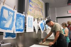 BK Skaggs, Shari Trennert, and Maylee Noah rinse their prints while others hang to dry. These prints show the first pass with the cyan layer.