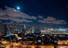 A lua aparece entre as nuvens e ilumina a noite sobre os prédios da cidade